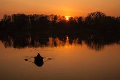 Silhouettes de la navigation romantique de couples dans un bateau contre le contexte du coucher du soleil orange image stock