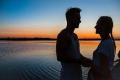 Silhouettes de la réjouissance de repos de jeunes beaux couples au lever de soleil près du lac Images libres de droits