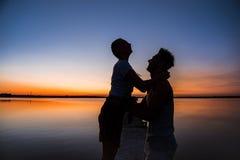 Silhouettes de la réjouissance de repos de jeunes beaux couples au lever de soleil près du lac Photos libres de droits