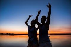 Silhouettes de la réjouissance de repos de jeunes beaux couples au lever de soleil près du lac Photographie stock