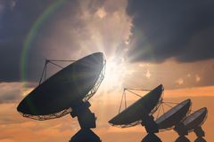 Silhouettes de la rangée d'antennes paraboliques ou d'antennes par radio au coucher du soleil Photos libres de droits