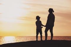 Silhouettes de mère et de fils au temps de coucher du soleil Images libres de droits