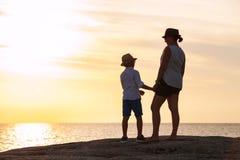 Silhouettes de mère et de fils au temps de coucher du soleil Photographie stock