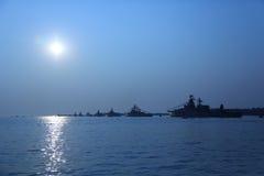 Silhouettes de navires de guerre dans le clair de lune Images stock
