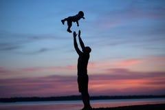 Silhouettes de père jetant son enfant en l'air Photo stock