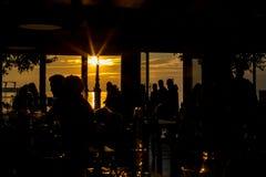 Silhouettes de personnes recueillant au lever de soleil dans la barre Photos stock