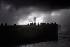 Silhouettes de personnes sur la jetée de mer voyant la tempête Photos stock