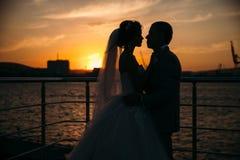 Silhouettes de portrait des jeunes mariés se tenant sur le fond de ville de nuit et regardant tendrement l'un l'autre le coucher  photos libres de droits