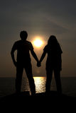 The silhouettes depict the love of couples with beautiful sunset backdrop. Stock Photography