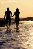 Silhouettes des amants au coucher du soleil Image stock