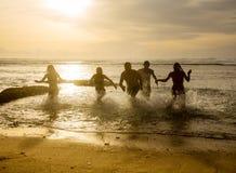 Silhouettes des amis sortant en courant de l'océan Images libres de droits