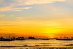 Silhouettes des bateaux à voile sur le fond de mer de coucher du soleil Photographie stock