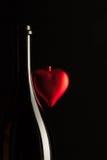 Silhouettes des bouteilles de vin élégantes avec le coeur rouge Photographie stock libre de droits