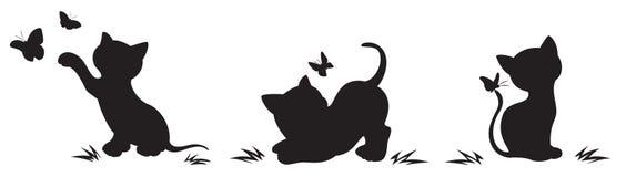 Silhouettes des chats avec des papillons Photographie stock