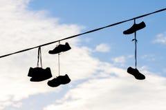 Silhouettes des chaussures accrochant sur le câble contre le ciel Images libres de droits