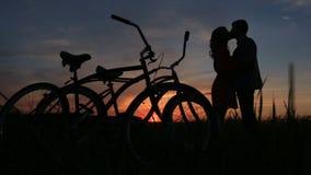 Silhouettes des couples affectueux embrassant tendrement dans le domaine pendant le coucher du soleil rouge et gris Promenade ave clips vidéos