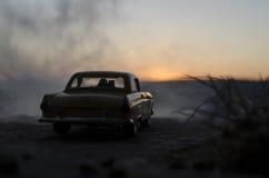 silhouettes des couples heureux se reposant dans la vieille voiture de vintage au temps de coucher du soleil L'effet d'installati Photographie stock libre de droits