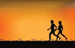 Silhouettes des coureurs de couples avec le beau ciel au coucher du soleil Images stock