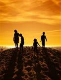 Silhouettes des enfants jouant à la plage Photographie stock