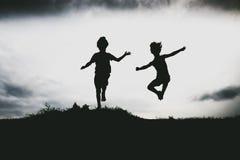 Silhouettes des enfants sautant d'une falaise de sable à la plage Photos stock