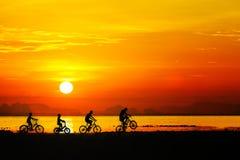 Silhouettes des enfants sur la bicyclette contre le ciel de coucher du soleil à l'être Photos stock