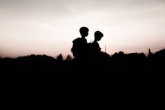 Silhouettes des enfants trimardant au coucher du soleil Images stock