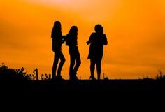 silhouettes des filles contre le ciel au coucher du soleil, Photographie stock