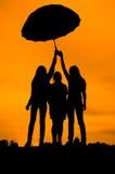 silhouettes des filles contre le ciel au coucher du soleil, au-dessous d'un parapluie Image libre de droits