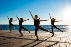 Silhouettes des filles folâtres dansant le zumba près de la mer au lever de soleil Images libres de droits