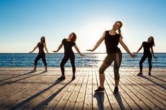 Silhouettes des filles folâtres dansant le zumba près de la mer au lever de soleil Photo libre de droits