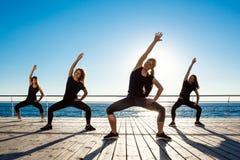Silhouettes des filles folâtres dansant le zumba près de la mer au lever de soleil Images stock
