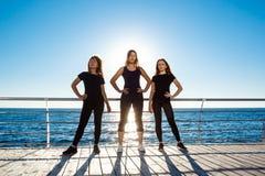 Silhouettes des filles folâtres dansant le zumba près de la mer au lever de soleil Photo stock