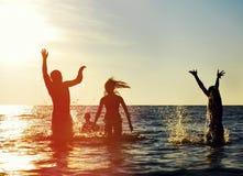 Silhouettes des gens branchant dans l'océan Photo libre de droits