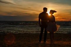 Silhouettes des hommes et des femmes dans la jupe courte luxuriante, atteignant I Image stock