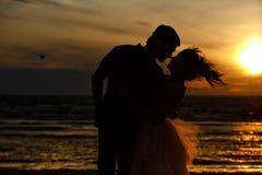 Silhouettes des hommes et des femmes dans la jupe courte luxuriante, embrassant l'AG Images libres de droits