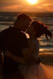Silhouettes des hommes et des femmes dans la jupe courte luxuriante, embrassant l'AG Image libre de droits