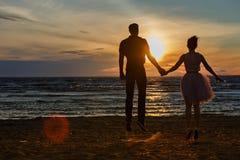 Silhouettes des hommes et des femmes dans la jupe courte luxuriante sautant  Photos libres de droits