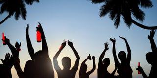 Silhouettes des jeunes célébrant, buvant sur une plage Photos libres de droits