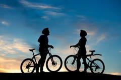 Silhouettes des jeunes dans l'amour au coucher du soleil Images stock