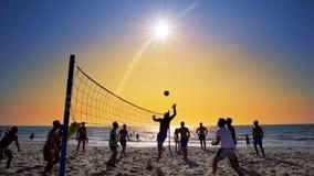 Silhouettes des jeunes hommes jouant le volleyball sur la plage de Varkala au coucher du soleil Images stock