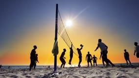 Silhouettes des jeunes hommes jouant le volleyball sur la plage de Varkala au coucher du soleil Images libres de droits