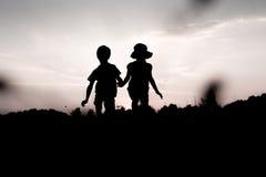 Silhouettes des jumeaux sautant outre d'une falaise au coucher du soleil Photos stock