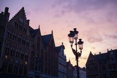Silhouettes des maisons de centre de la ville à Bruges contre le coucher du soleil Photo stock