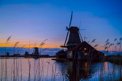 Silhouettes des moulins néerlandais près du lac au coucher du soleil photographie stock