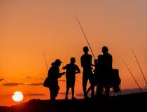 Silhouettes des pêcheurs au coucher du soleil Photos libres de droits