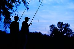 Silhouettes des pêcheurs avec les cannes à pêche sur le fond de la nature Photo libre de droits