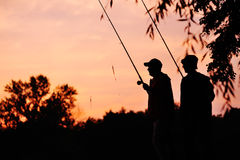 Silhouettes des pêcheurs avec les cannes à pêche sur le fond de la nature Photographie stock libre de droits
