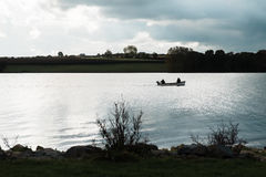Silhouettes des pêcheurs dans le bateau en Rutland Water, Angleterre Photos libres de droits