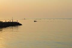 Silhouettes des pêcheurs sur le brise-lames après lever de soleil Photographie stock libre de droits