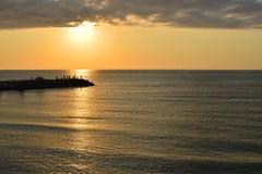 Silhouettes des pêcheurs sur le brise-lames après lever de soleil Photo libre de droits